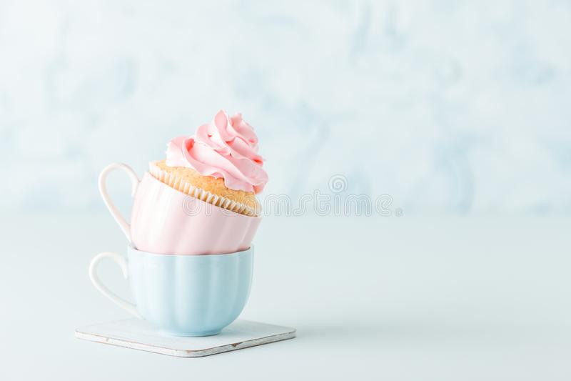 Queque com a decoração de creme cor-de-rosa delicada em dois copos no fundo pastel azul imagens de stock royalty free