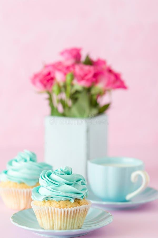 Queque com a decoração do creme da hortelã e o ramalhete doces de rosas vermelhas no vaso chique gasto retro no fundo pastel cor- imagem de stock