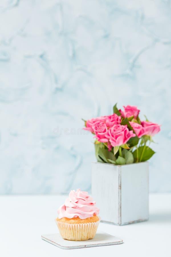 Queque com decoração e o ramalhete cor-de-rosa das rosas no vaso chique gasto retro azul imagens de stock royalty free