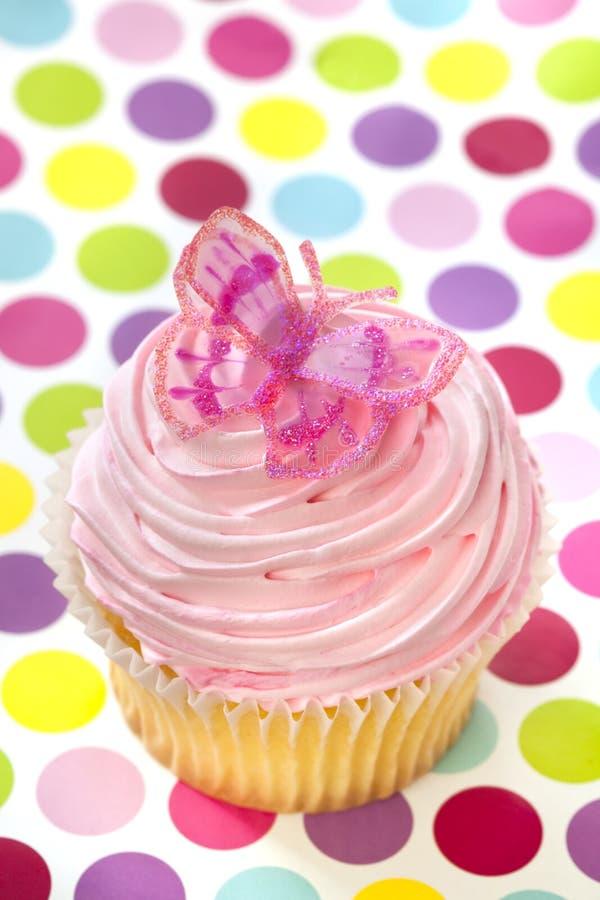 Queque cor-de-rosa com borboleta imagem de stock