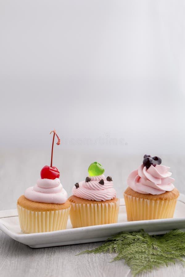 Queque cor-de-rosa com cereja vermelha, molhos do mirtilo, geleia verde imagens de stock royalty free