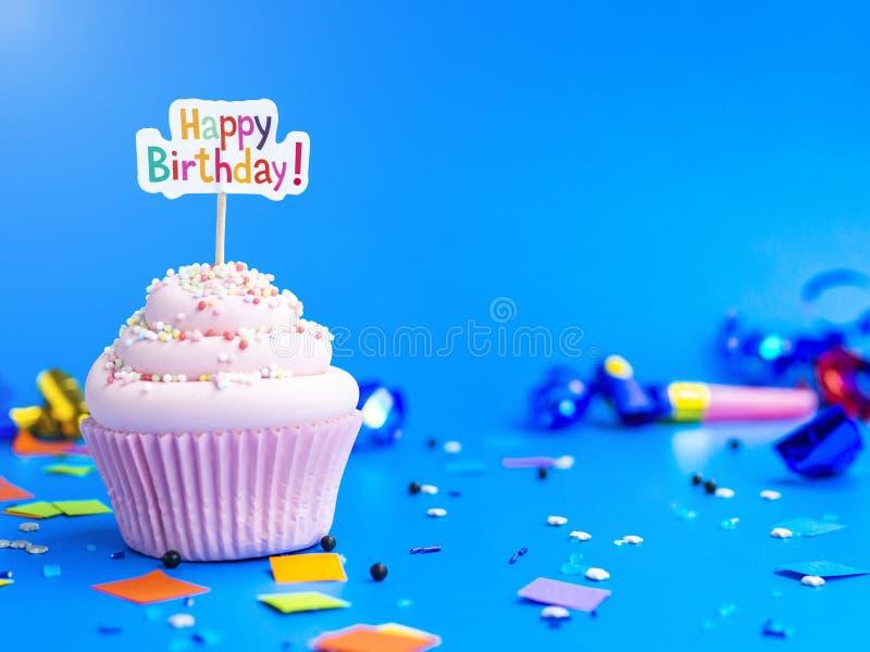 Queque cor-de-rosa com texto do feliz aniversario em um fundo azul imagem de stock royalty free