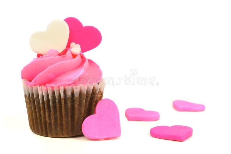 Queque cor-de-rosa do dia de Valentim com corações dos doces foto de stock