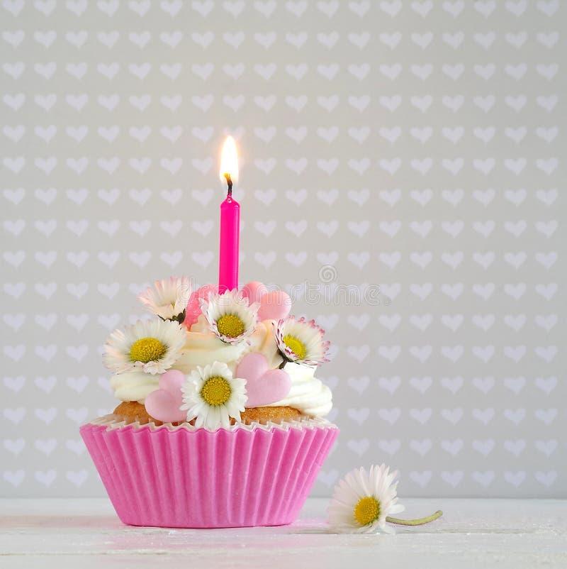 Queque cor-de-rosa do manteiga-creme com margaridas e vela imagens de stock royalty free