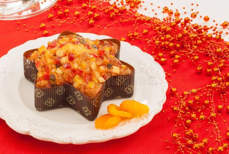 Queque de frutas con las frutas escarchadas en fondo de la Navidad foto de archivo libre de regalías