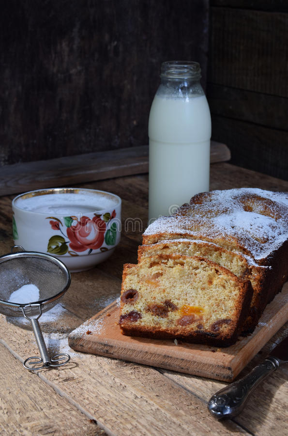 Queque de frutas tradicional con las pasas, albaricoques secados, cereza para la Navidad en fondo de madera Torta y leche recient imagen de archivo libre de regalías