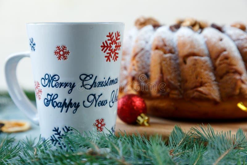 Queque de frutas tradicional para la Navidad adornado con el azúcar en polvo y las nueces, pasas al lado de la taza de café imagenes de archivo