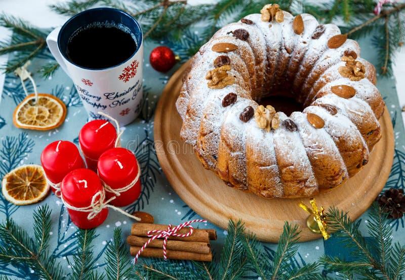 Queque de frutas tradicional para la Navidad adornado con el azúcar en polvo y nueces, pasas y taza de café o de té Delicioius he foto de archivo libre de regalías