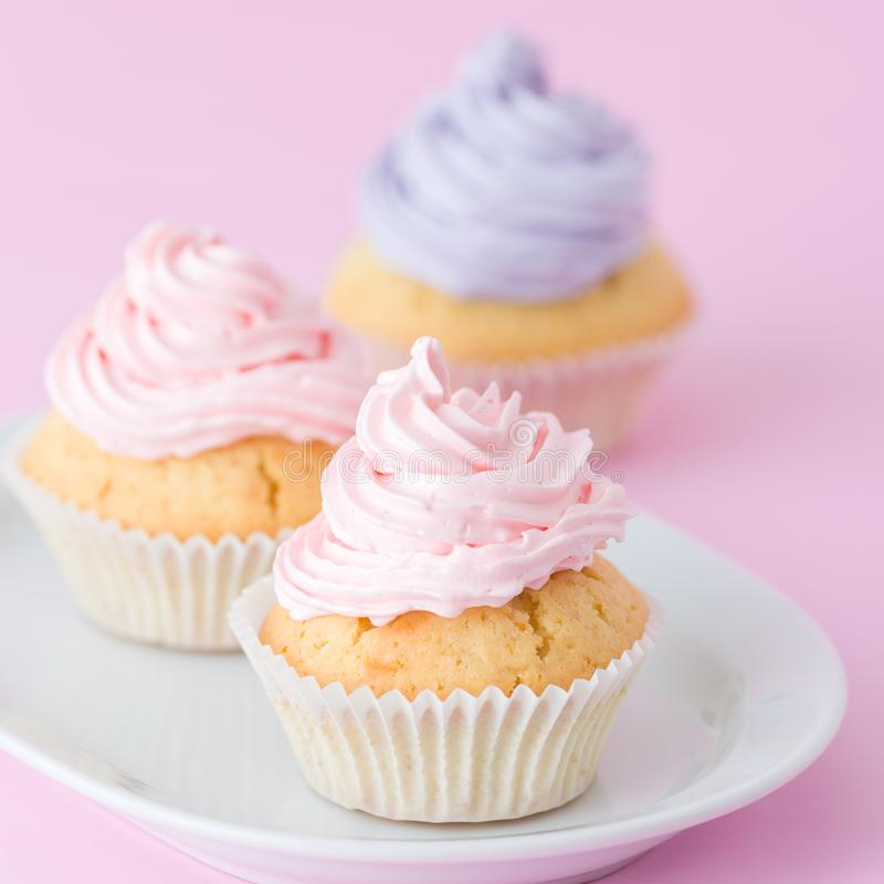Queque decorado com buttercream cor-de-rosa e violeta no fundo do rosa pastel Bolo bonito doce Bandeira quadrada, cartão f fotos de stock royalty free