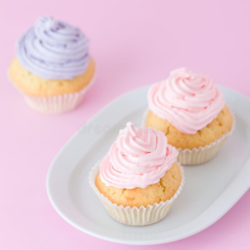 Queque decorado com buttercream cor-de-rosa e violeta no fundo do rosa pastel Bolo bonito doce Bandeira quadrada, cartão f foto de stock