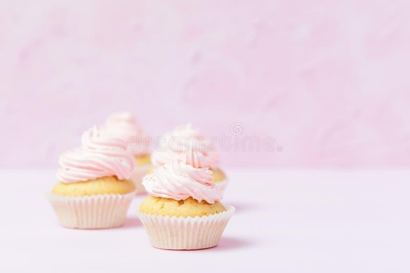 Queque decorado com buttercream cor-de-rosa no fundo do rosa pastel Bolo bonito doce Bandeira horizontal, cartão para o birt imagens de stock royalty free