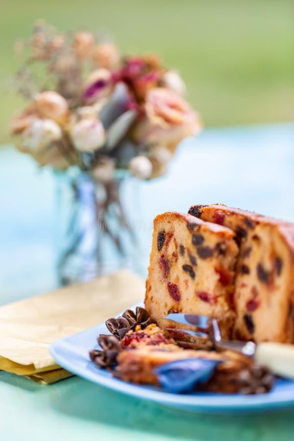 Queque do bolo de frutas ou das fatias e ramalhete obscuro das flores em uma placa azul Sobremesa fotos de stock