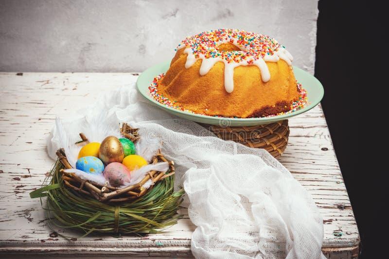 Queque do feriado, ovos coloridos em um ninho, feriado tradicional cristão da Páscoa foto de stock royalty free
