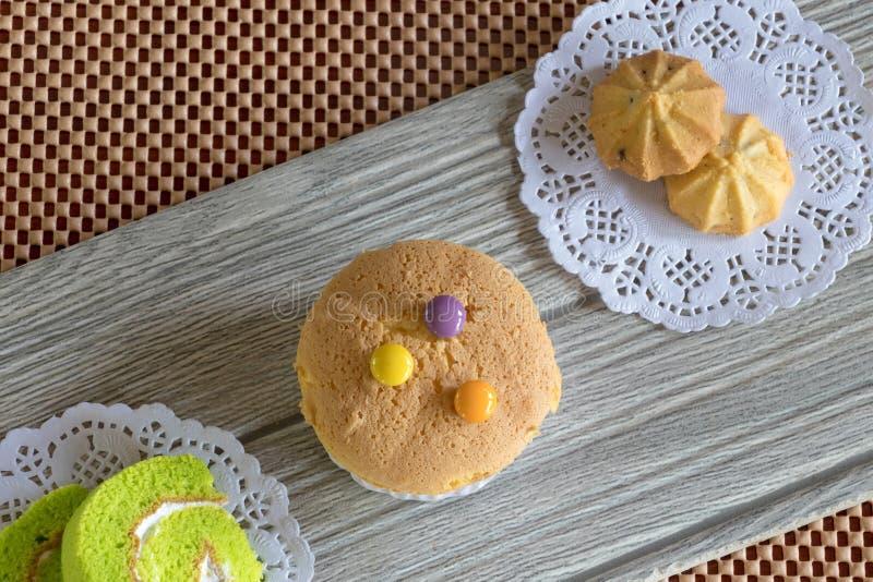 Queque e cookie do rolo do bolo na tabela de madeira fotografia de stock
