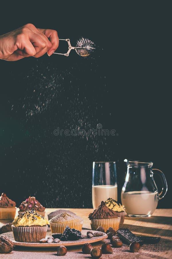 Queque e queques do chocolate com enchimento do açúcar pulverizado em uma placa de madeira fotos de stock