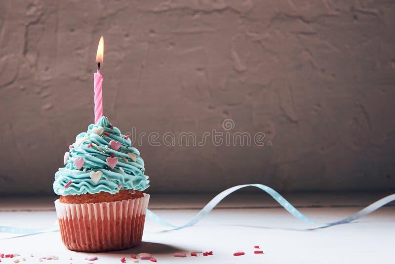 Queque ou um bolo pequeno com uma vela ardente conceito das felicitações, feriado fotografia de stock