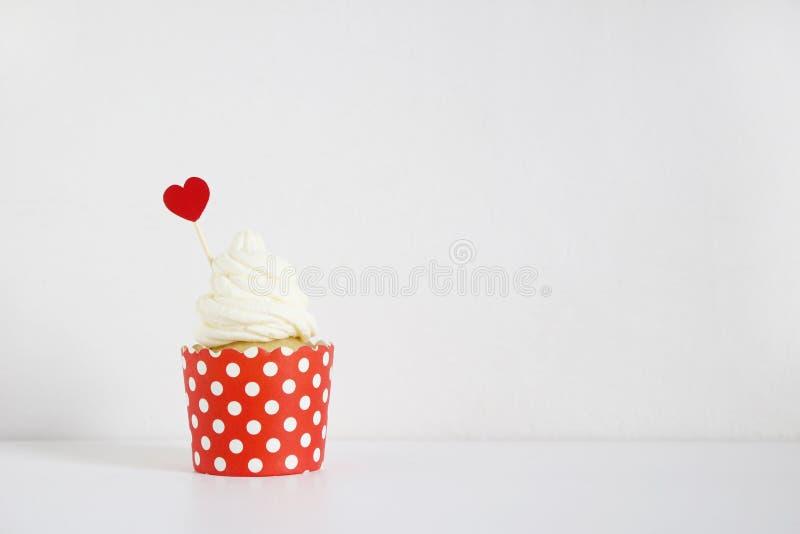 Queque saboroso com a decoração de papel vermelha do coração na tabela branca Aniversário, casamento ou de partido do Valentim al imagens de stock royalty free
