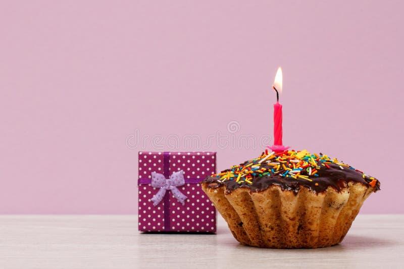 Queque saboroso do aniversário com queimadura da vela e da caixa de presente festivas imagem de stock royalty free