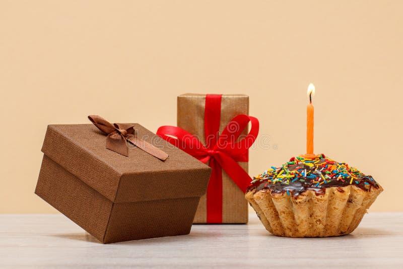Queque saboroso do aniversário com queimadura da vela e de caixas de presente festivas fotos de stock