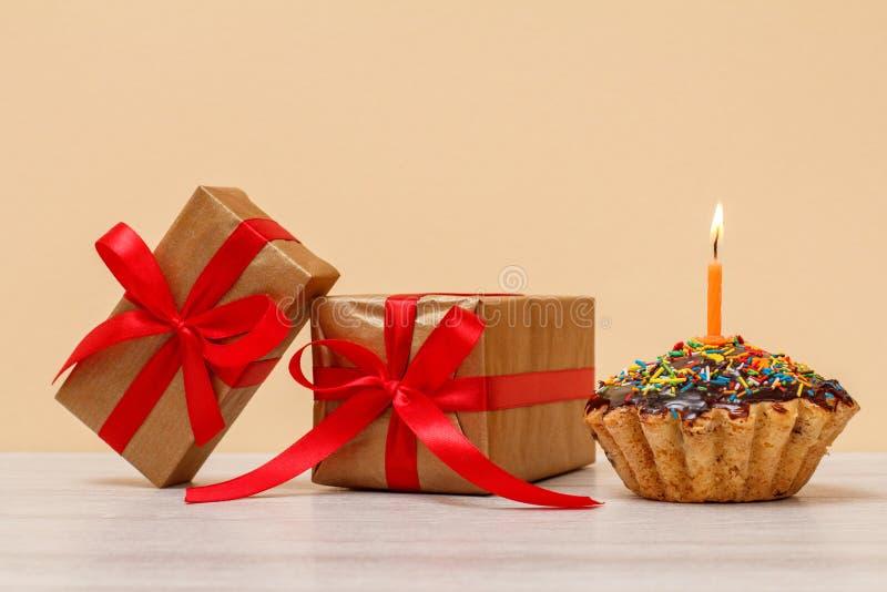 Queque saboroso do aniversário com queimadura da vela e de caixas de presente festivas foto de stock royalty free