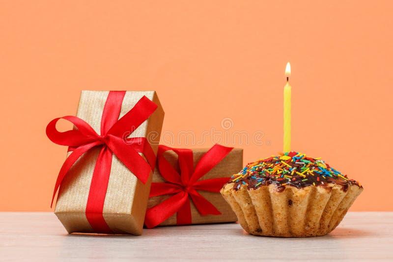 Queque saboroso do aniversário com queimadura da vela e de caixas de presente festivas fotografia de stock royalty free