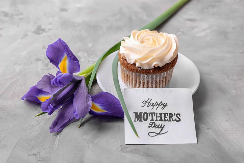 Queque saboroso, flor e cartão com DIA de MÃE FELIZ das palavras no fundo cinzento imagem de stock