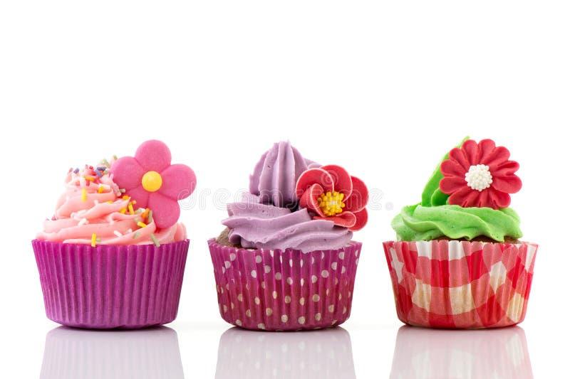 Queques coloridos com flores fotografia de stock royalty free