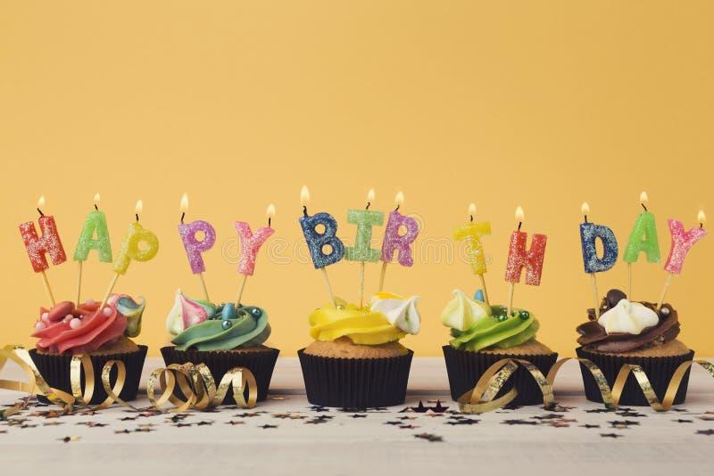 Queques com as velas que soletram o feliz aniversario da palavra imagens de stock royalty free