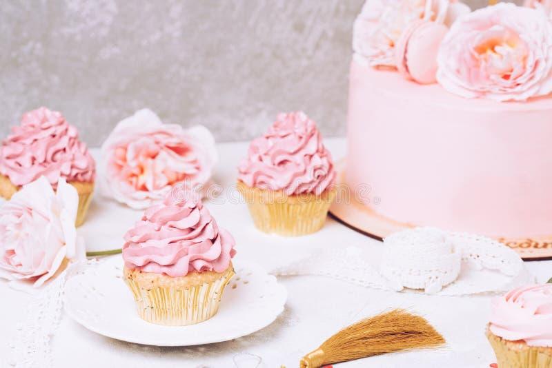 Queques cor-de-rosa com rosas e bolo do feriado Festivo e brilhante Conceito da celebração do casamento fotografia de stock