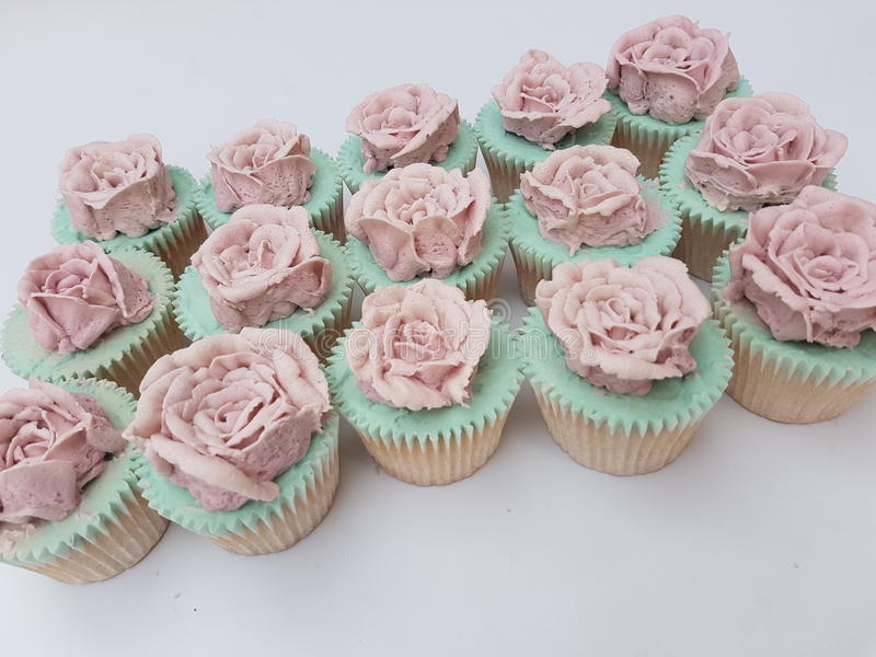 Queques cor-de-rosa conduzidos mão do vintage do buttercream fotos de stock