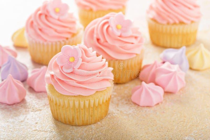 Queques da baunilha com a geada cor-de-rosa da framboesa foto de stock royalty free