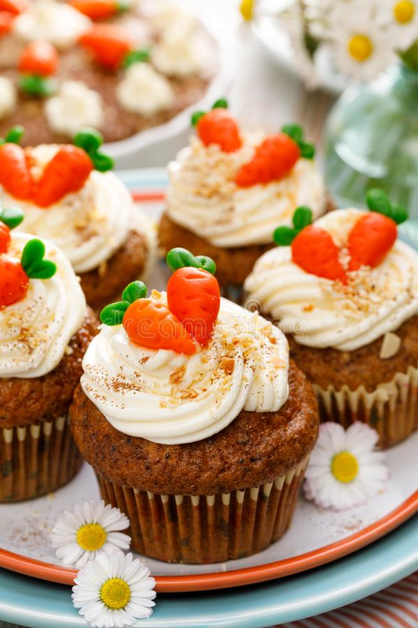 Queques da cenoura com o creme do mascarpone decorado com cenouras do maçapão em uma placa imagens de stock royalty free