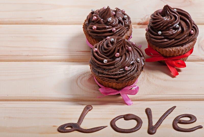 Queques do chocolate com creme do chocolate em um fundo de madeira fotografia de stock royalty free