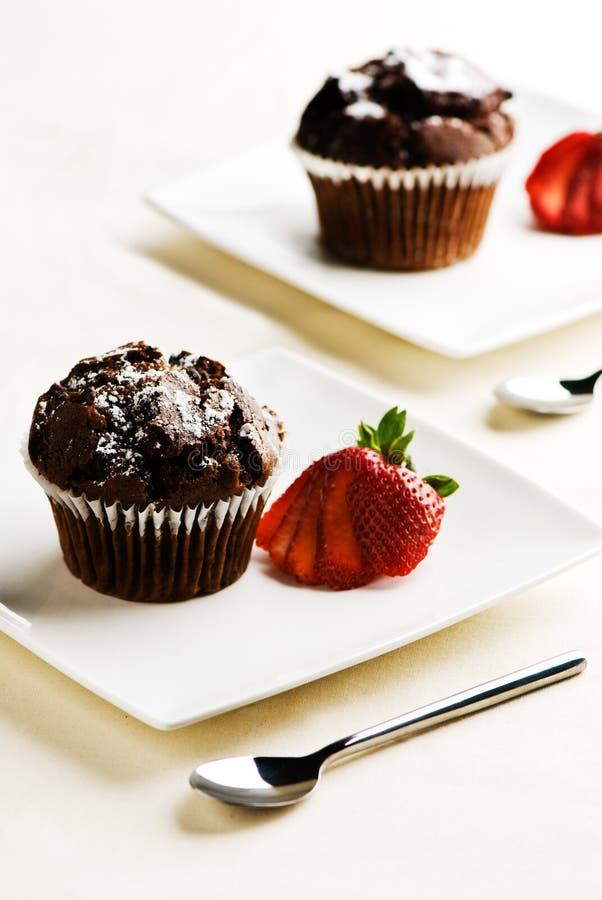 Queques do chocolate com morangos fotografia de stock royalty free