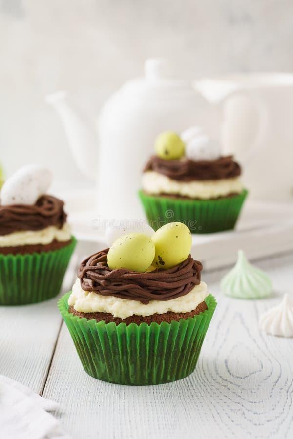 Queques do chocolate da Páscoa decorados com os ovos do ninho e de doces imagem de stock