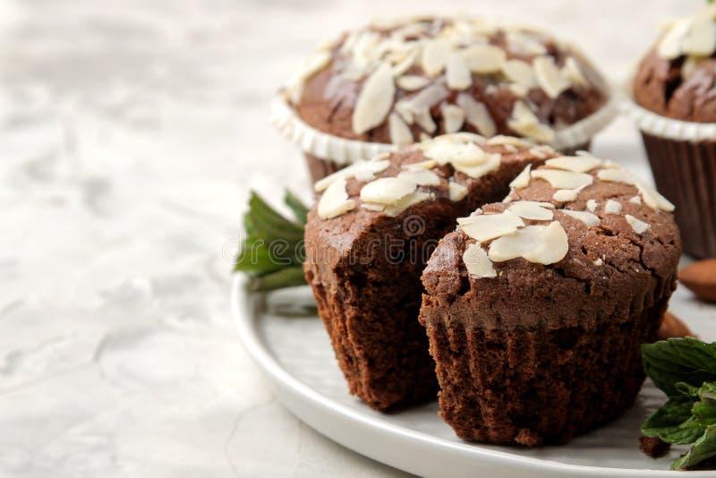 Queques do chocolate delicioso, doce, com as p?talas da am?ndoa ao lado das porcas da hortel? e da am?ndoa em uma tabela do bet?o foto de stock