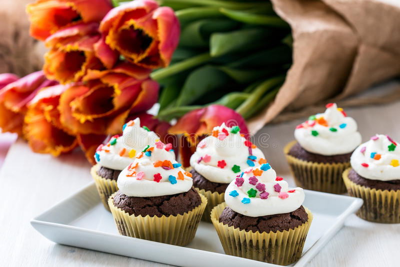Queques do chocolate do dia de mães com tulipas da mola foto de stock royalty free