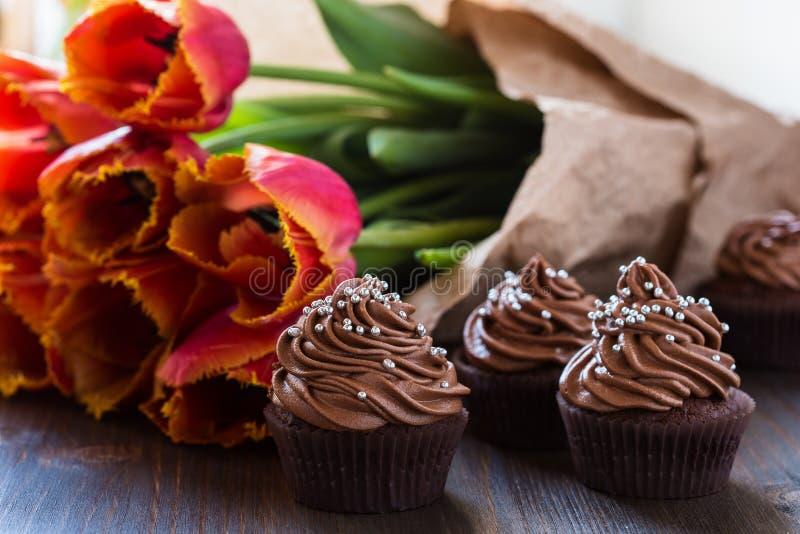 Queques do chocolate do dia de mães com tulipas da mola fotografia de stock