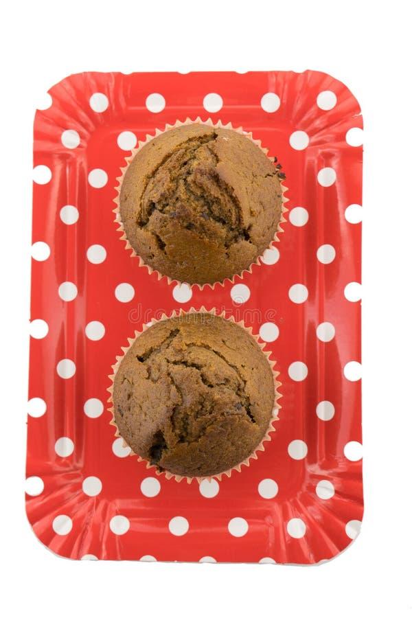 Queques do chocolate na placa vermelha no fundo branco fotos de stock royalty free