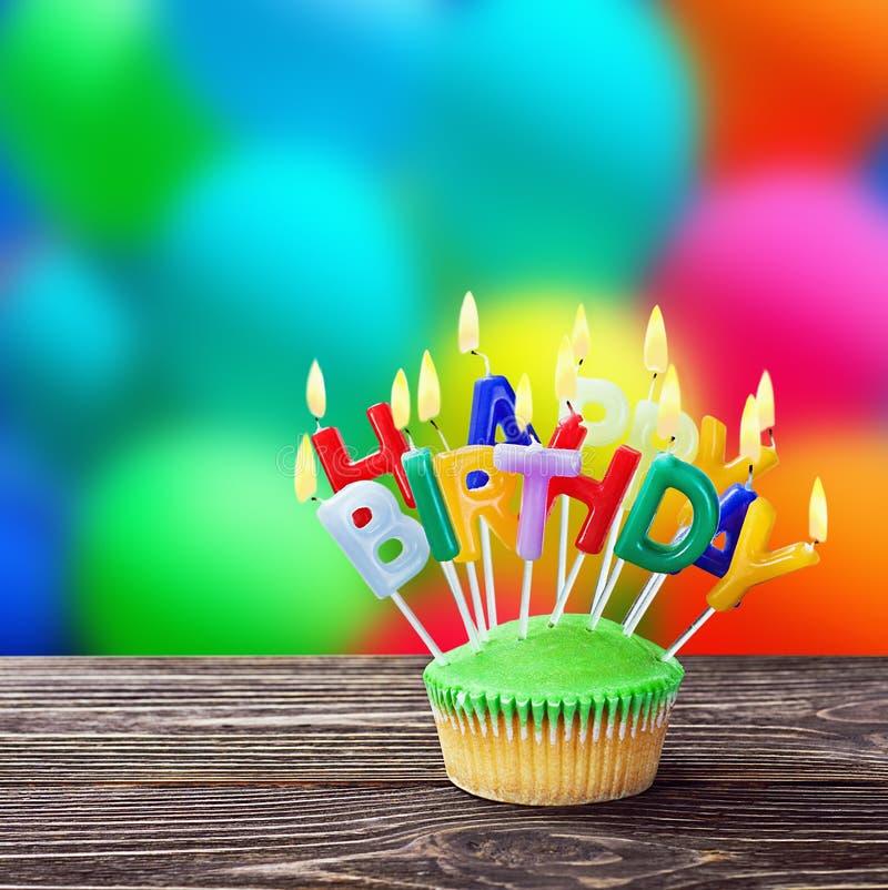 Queques do feliz aniversario com velas fotografia de stock royalty free