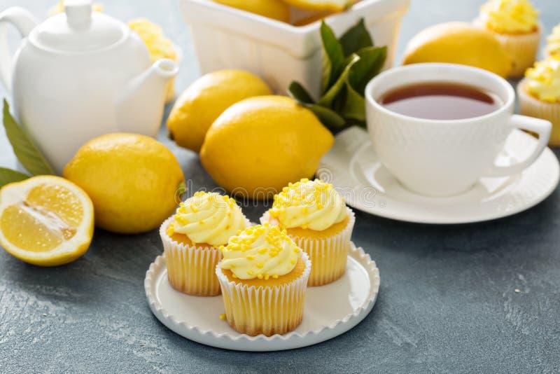 Queques do limão com a geada amarela brilhante imagens de stock