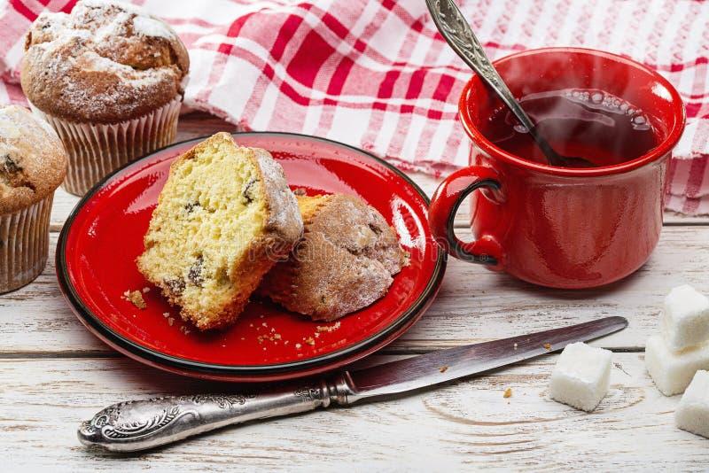Queques frescos do café da manhã e chá quente no copo vermelho fotos de stock