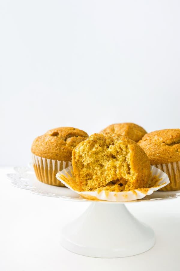 Queques inteiros cozidos casa da abóbora do farelo de trigo no suporte do bolo branco Conceito saudável do cozimento da pastelari foto de stock