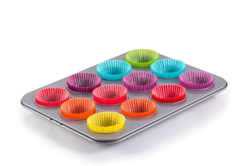Queques que cozem a bandeja com as caixas de papel coloridas imagem de stock royalty free