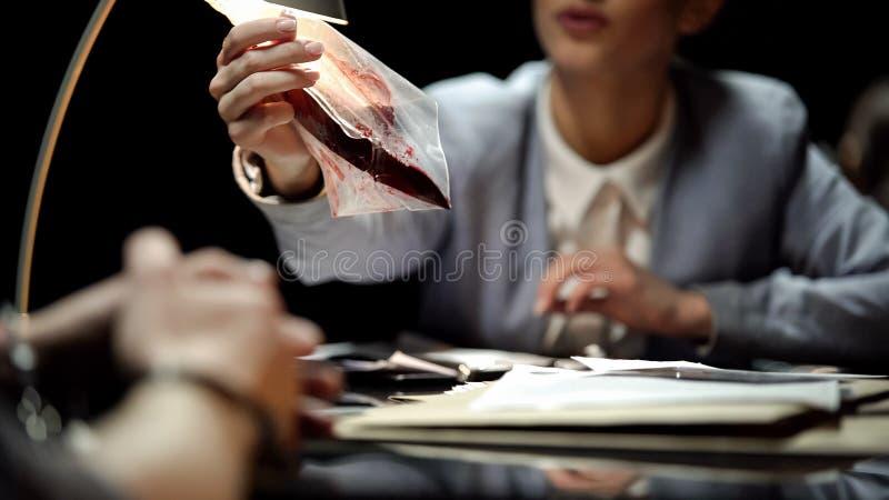 Querellante de sexo femenino que muestra el cuchillo con la sangre al sospechoso, para confesión que espera fotos de archivo libres de regalías