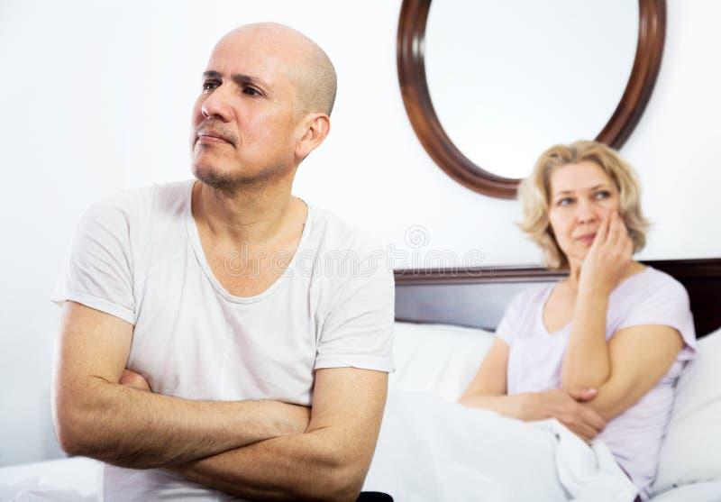 Querelles mûres de couples dans le lit photo stock