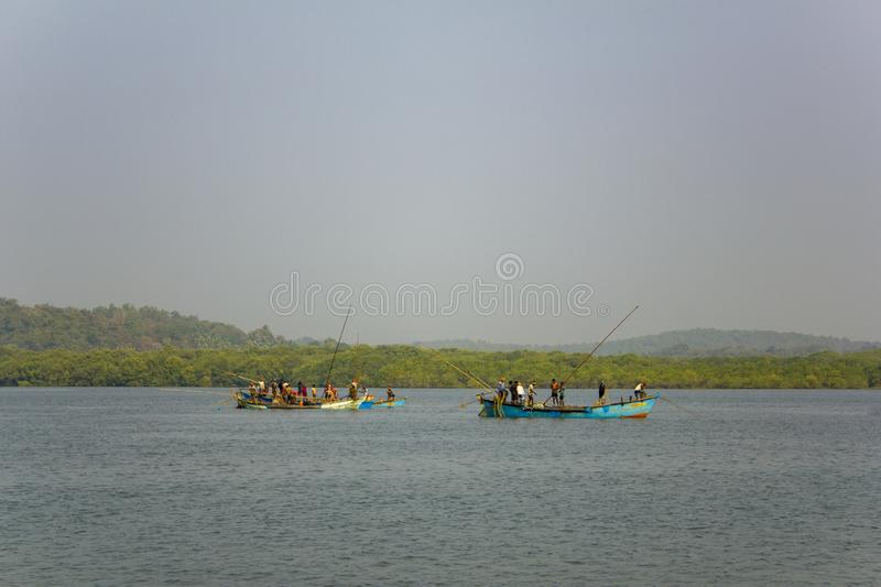 Indian men extract sand in the river way. two boats with people in the water against the backdrop stock photography