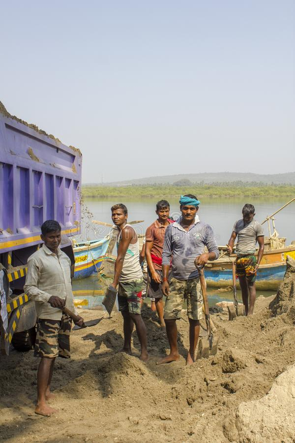 Indian men load sand into a truck with shovels on the background of the river stock images