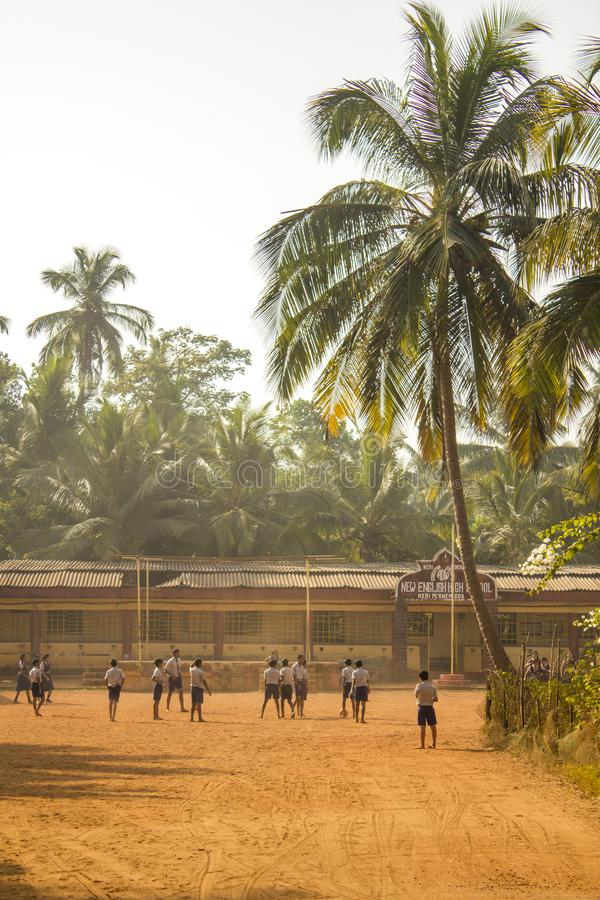 Indian schoolchildren playing football in the courtyard of the school on a yellow ground against royalty free stock photos