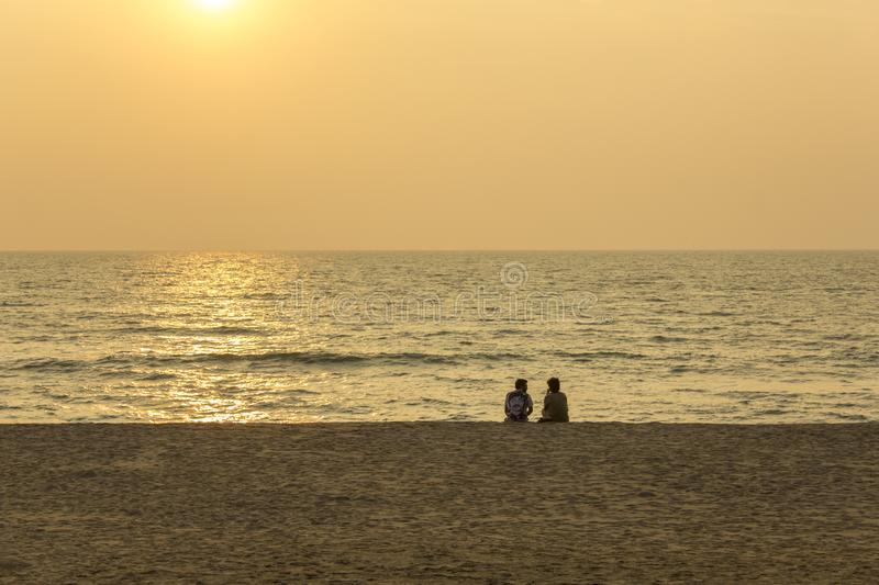 Two men are sitting on an empty sandy beach against the background of the ocean and the evening royalty free stock photos